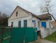 Малоприметный одноэтажный дом с синими рамами.